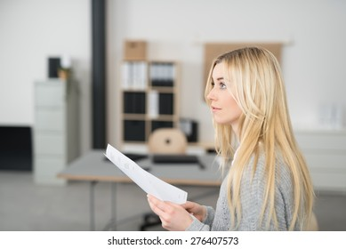 Thoughtful Pretty Young Woman with Long Blond Hair Holding a Paper Inside the Office While Looking to the Upper Left of the Frame, Captured in Side View.