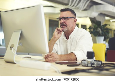 Thoughtful professional it developer thinking on installing new programs for software update.Mature man 40 years old sitting in office at modern computer and pondering on new project