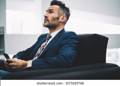 Thoughtful proud ceo looking up while thinking on important text answer in message sitting on couch with smartphone in hands.Pondering mature businessman in formal wear chatting on cellular in office