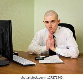 Thoughtful puzzle office manager sits at table with documents and computer
