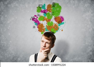 Thoughtful redhead student planning your day. Tasks algorithm and multitasking. Creativity and problem solving. Strategy formulation process. Boy on background of grey wall with doodles overhead.