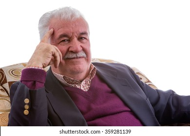 Thoughtful retired elderly gentleman staring at the camera with a speculative serious expression as he relaxes in a comfortable armchair, isolated on white with copy space