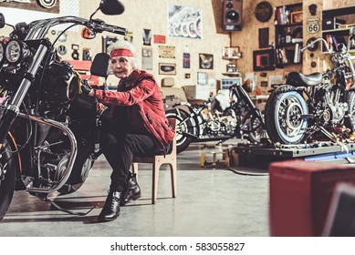 Thoughtful retiree cleaning motorcycle in mechanic shop