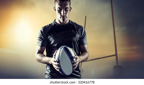 Thoughtful rugby player holding ball against goals posts