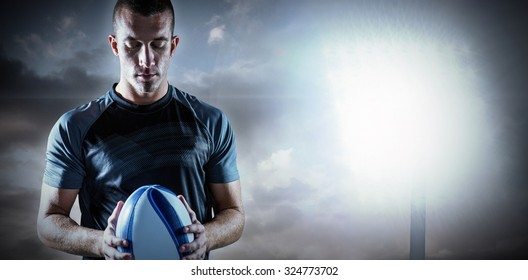 Thoughtful rugby player holding ball against spotlight in sky