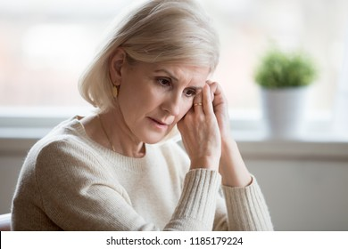 Thoughtful sad mature middle aged woman feeling blue melancholic worried concerned about problems, upset serious depressed senior old lady widow thinking of anxiety depression, grieving lost love