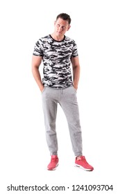 Thoughtful sad sporty man in leisurewear with hands in pockets looking up. Full body isolated on white background.