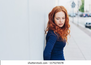 Thoughtful sad young woman with downcast eyes leaning against a white exterior wall in a town street with copy space