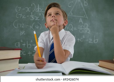 Thoughtful schoolboy doing his homework in classroom