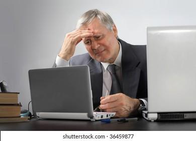 thoughtful senior business man using laptop