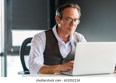 Thoughtful senior businessman typing on notebook