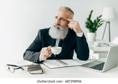 thoughtful senior businessman at workplace in modern office