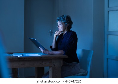 Thoughtful senior businesswoman working on digital tablet until late. Mature woman examining business report on laptop screen. Senior woman in formals using digital tablet at home during the night.