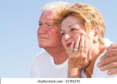 thoughtful senior couple hugging