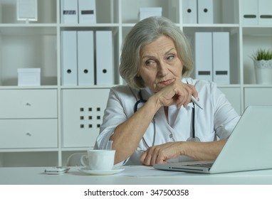 Thoughtful senior doctor sitting at table with laptop in office