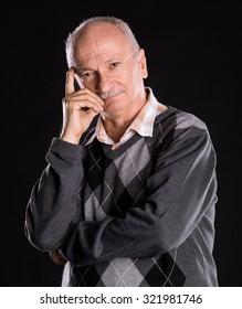 Thoughtful senior man on a dark background