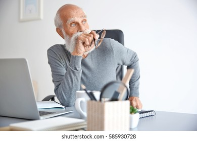 Thoughtful senior man sitting with laptop in office