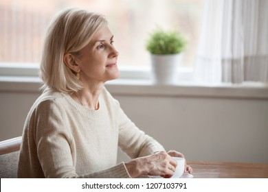 Thoughtful senior woman drinking coffee or tea dreaming about something, dreamy aged female enjoying free time at home, thinking about pleasant memories, reminiscent elderly lady leisure morning