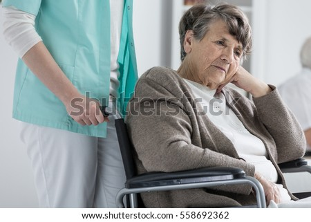 Thoughtful senior woman on a wheelchair
