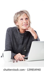 Thoughtful senior woman sitting at a desk with her chin on her hand looking upwards with a laptop open in front of her, on white