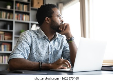 Thoughtful serious african professional business man sit with laptop thinking of difficult project challenge looking for problem solution searching creative ideas lost in thoughts at home office desk - Shutterstock ID 1626375460
