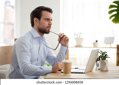 Thoughtful serious businessman lost in thoughts at work with laptop, focused executive thinking of problem solution, worried puzzled manager pondering question or solving business issues at workplace