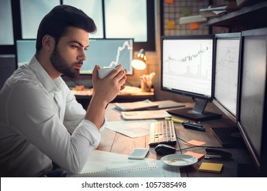 Thoughtful serious trader broker drinking coffee analyzing stock market graphs