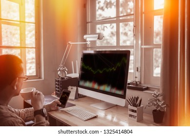 Thoughtful serious trader drinking coffee analyzing stock market graphs