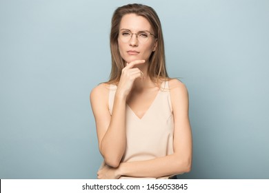 Thoughtful serious woman in glasses touching chin with fingers, looking at camera, pensive female pondering something, planning, problem solution, lost in thoughts, isolated on studio background