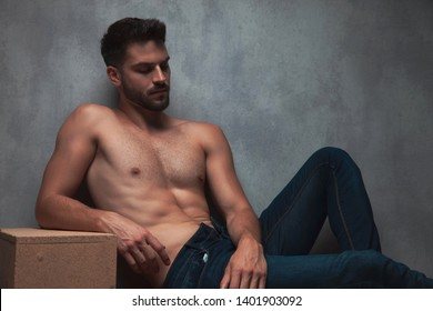 Thoughtful shirtless guy relaxing and looking down while leaning on a box and on gray studio background