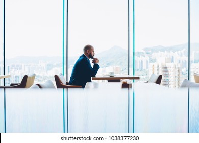 Thoughtful smart male entrepreneur dressed in corporate suit thinking on important business solution sitting alone at cup of coffee in cafeteria with glass windows.Pensive entrepreneur making decision