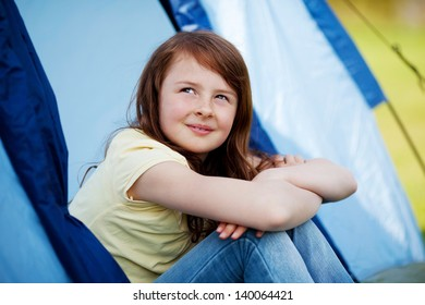 Thoughtful smiling girl looking up while sitting in tent