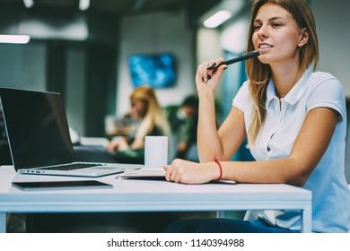 Thoughtful smiling young woman with pen in hand looking away while thinking on creative idea for writing essay sitting at desktop with modern laptop computer with mock up area in office