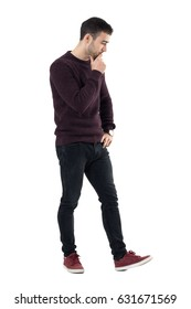 Thoughtful stressed casual man walking and looking down. Full body length portrait isolated over white studio background.