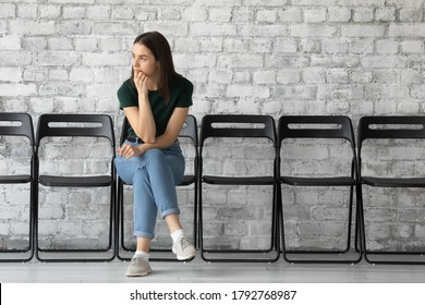 Thoughtful stressed unemployed young woman candidate waiting for job interview or hr manager employer decision, sitting on chair alone in empty office hall, feeling nervous, recruitment concept