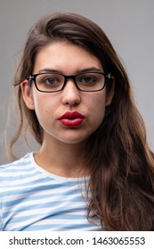 Thoughtful studious young woman wearing glasses staring intently at the camera with parted lips over a grey studio background