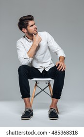 Thoughtful stylish attractive casual young man sitting on chair over gray background