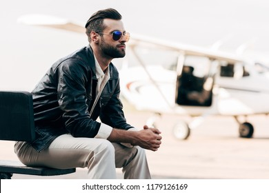 thoughtful stylish man in leather jacket and sunglasses sitting on bench