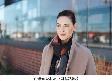 Thoughtful stylish woman with a faraway expression standing in front of a commercial building in town