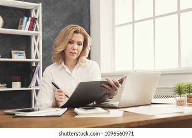 Thoughtful successful businesswoman in formal wear sitting at wooden desk in modern office and reading report document, copy space