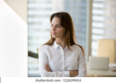Thoughtful successful motivated businesswoman looking away dreaming of future in office, confident millennial female boss thinking about business vision enjoying success or planning new goals