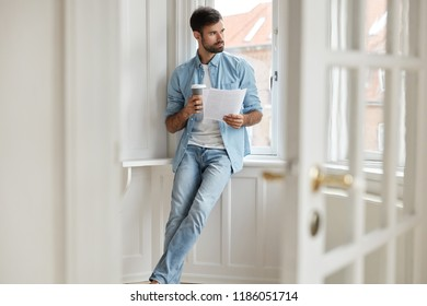 Thoughtful sucessful manager thinks on realization of goods, holds documentation or official record, dressed in casual clothes, works at home, drinks takeaway coffee. Cozy apartment. Career concept.