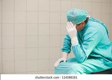Thoughtful surgeon sitting in a operating room with his hand on head