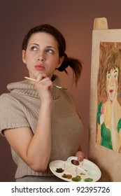 Thoughtful teenage girl painting a picture