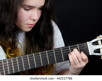 Thoughtful teenage girl playing a black guitar (on a black background), selective focus on the fingers and guitar neck