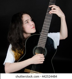 Thoughtful teenage girl playing a black guitar (on a black background)