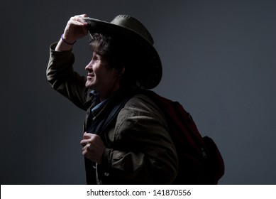 Thoughtful traveler in a hat looking to the side. A man with a backpack