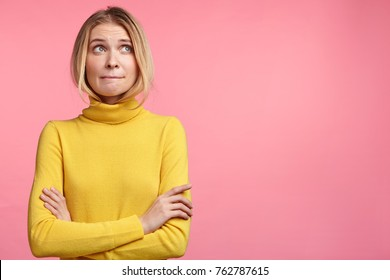 Thoughtful uncertain female presses lips, keeps hands crossed, anticipates something, looks upwards, has hesitant expression, models against pink bakground with copy space for advertising content