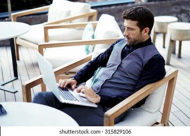 Thoughtful wealthy businessman work on-line on net-book while sits at modern restaurant terrace, young intelligent rich man connecting to wireless via laptop computer during work break in coffee shop