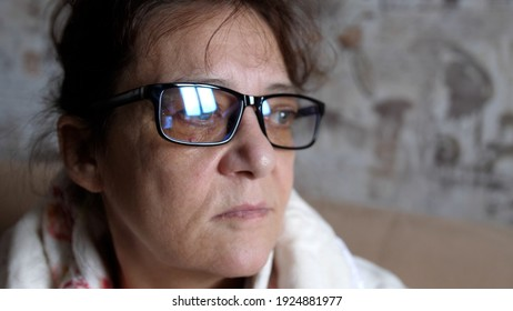 Thoughtful woman in 60s in glasses looking out window absorbed in problems and difficulties. 3840x2160